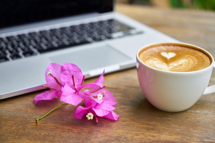 "This is the header image for a blog post about ""Retiring My Blog"". It shows a cup of cappacino with a heart swirled in the top. Beside the white cup is a beautiful pink flower. Behind it is a laptop - open. Everything is on a wooden table."